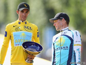 Lance Armstrong (right) looks on after Alberto Contador is handed the Tour de France trophy in Paris.