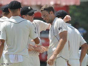 Vettori receives the congratulations of teammates after taking his 300th Test wicket.