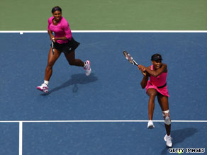 Serena Williams, back left, watches as Venus hits a backhand during their doubles semifinal victory.