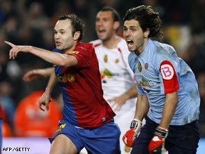 Iniesta (left) celebrates his important goal for Barcelona as Lux protests.