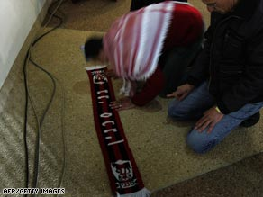 Bnei Sakhnin fans pray on their team's scarf before a game.