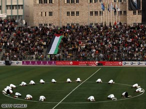 The Palestinian players pray before their historic match with Jordan in the Al-Husseini Stadium.