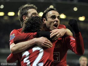 Berbatov (right) is congratulated after his late goal put Manchester United top of the Premier League.