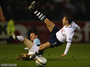 Tottenham winger David Bentley (right) is sent flying as the Carling Cup holders scraped into the final again.