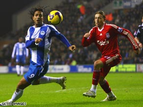 Mido (left) scored a vital equalizer on his Wigan debut to dent Liverpool's Premier League title challenge.