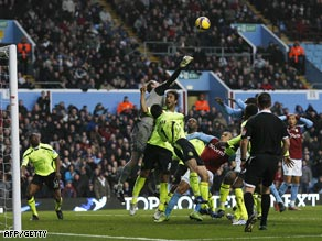 Wigan goalkeeper Chris Kirkland punches the ball clear under strong Villa pressure.