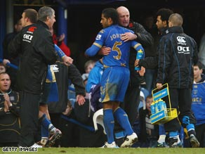 Johnson is hugged by caretaker manager Paul Hart after scoring Portsmouth's first goal.