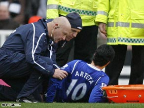 Arteta is attended to after injuring his knee in Sunday's draw at Newcastle.