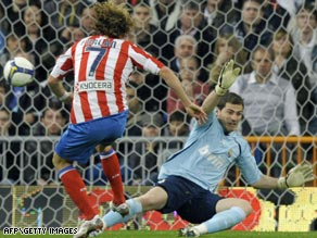 Diego Forlan fires the goal that brought an end to Real Madrid's 10-macth La Liga winning streak.