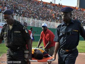 Police carry an injured person away from the football stadium in Abidjan on Sunday.