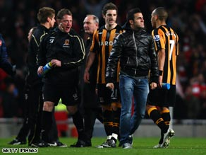 Fabregas struts past Hull players and coaches after Arsenal's 2-1 win at the Emirates.