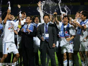 Japan players and management share a champagne moment after their 1-0 win.