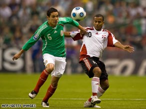 Mexico's match-winner Oscar Rojas tussles with Trinidad and Tobago's goalscorer Hayden Tinto.