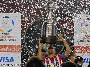 Juan Sebastian Veron is showered in confetti in Belo Horizonte, Brazil, as he hoists the Copa trophy.