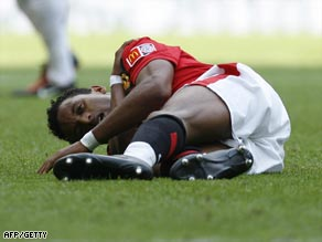 Nani clutches his shoulder after going down under a challenge from John Terry at Wembley.