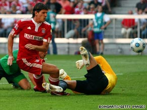 Mario Gomez bundles the ball past Bremen goalkeeper Tim Wiese to earn Bayern a point.