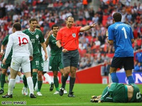 Referee Eriksson points to the spot as Slovenian players protest.