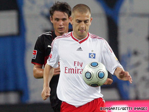 Hamburg goalscorer Mladen Petric holds off Stuttgart's Christian Trasch during his side's 3-1 win.