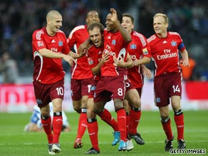 Hamburg's players mob Ze Roberto after his third goal in the Olympic Stadium.