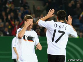 Ozil and Podolski celebrate Germany's late equalizer in their 1-1 draw against Finland in Hamburg.