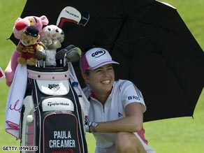 Creamer takes shelter under an umbrella as she waits to play a shot in Singapore.
