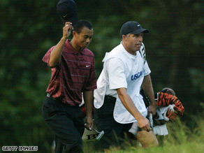 Tiger Woods and his caddie walk up to the 18th green on the Black Course at Bethpage State Park in 2002.