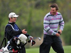 Derksen shares a joke with his caddie at a windswept Pinx Golf Club.
