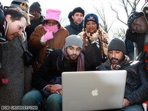 A group crowds around a laptop to watch the inaugural events in Washington.