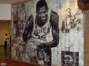 The same mural, seen from a different angle, displays a new set of images around the main figure.