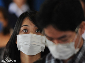 Passengers wear protective masks as they arrive Wednesday at Los Angeles International Airport.