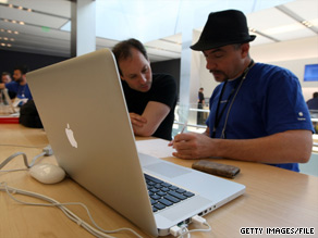 A worker helps a customer with a MacBook Pro laptop at an Apple store in San Francisco, California.