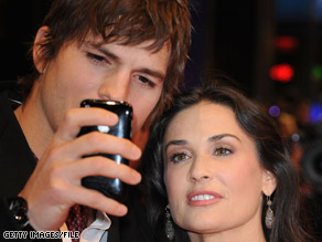 Ashton Kutcher shows Demi Moore something on his Apple iPhone using the touch screen.