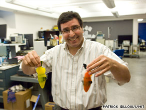 Nice catch! MIT engineer Kamal Youcef-Toumi displays two of his robot fish.