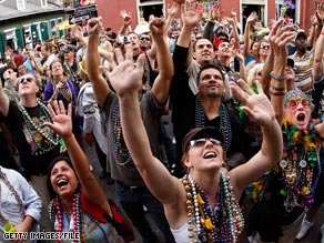 A crowd of people try to catch beads on Bourbon Street on Fat Tuesday last year.