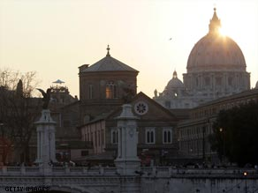 The sun sets behind St. Peter's Basilica on a beautiful spring day in Rome.
