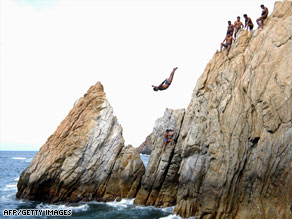 "A cliff diver jumps from ""La Quebrada"" cliff in Acapulco, Mexico. The diving is a popular tourist attraction."