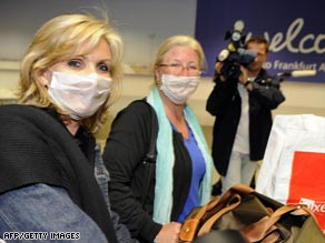 Two women wear face masks as they arrive at Germany's Frankfurt International Airport from Mexico City.