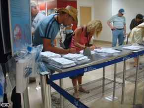Travelers leaving a Mexican airport fill out questionnaires about their health.