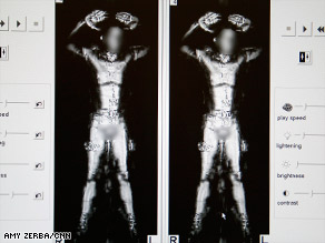 A TSA employee, shown from the back, as he stands in an airport whole-body imaging machine.