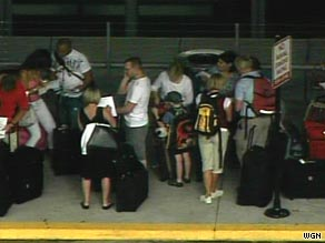 United Airlines passengers wait in line Thursday at O'Hare International Airport in Chicago.