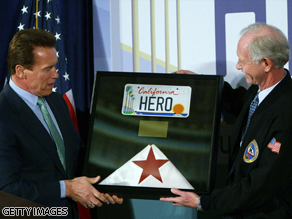 Gov. Arnold Schwarzenegger gives hero pilot Chesley Sullenberger a flag and license plate.