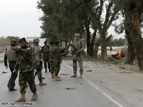 Afghan and U.S. soldiers walk at the site of a suicide attack outside Jalalabad in Nangarhar province Sunday.