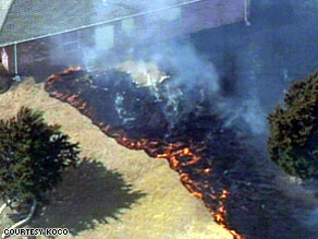 Wildfire threatens a house in Edmond, Oklahoma, on Friday.