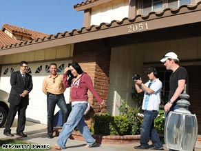 Nadya Suleman, the mother of octuplets, walks outside her new house for a video crew Tuesday.