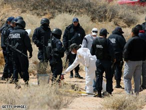 Federal police investigate a crime scene in Juarez. There have been about 1,000 drug-related deaths in Mexico so far this year.