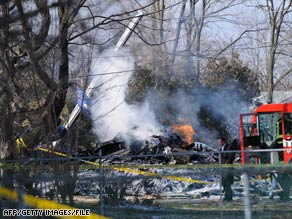An investigator walks past the wreckage from a plane crash in Clarence Center, New York, in February.