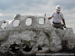 Personal effects are removed from the site of an airline disaster.