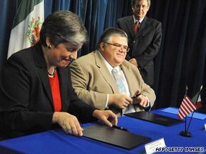 U.S. Homeland Security Secretary Janet Napolitano and Mexican offical Agustin Carstens sign a pact Monday.