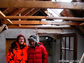 Jon Brumit and his wife, Sarah, in their new home shortly after buying it, under the huge hole in the roof.