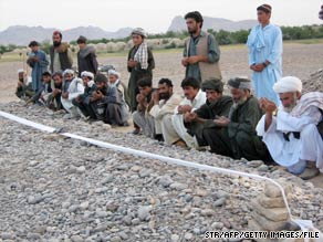 Villagers pray at a mass grave in early May after an airstrike in Afghanistan's Farah Province.
